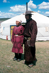Photograph of Tcevelmah standing with a man, both wearing traditional Mongolian clothing and boots.