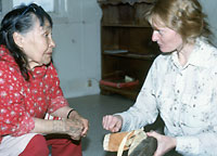 Photograph of Dr. Jill Oakes talking with Yupik boot maker Lillian Apangalook during a field expedition to Alaska in 1989.