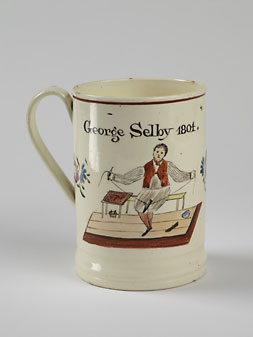 Ceramic tankard with an animated image of a shoemaker indicates some of the joy and social aspects of the shoemaking profession.  The inscription says, May shoemakers flourish and trade increase/and victory gain/Everlasting peace.