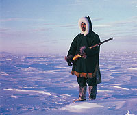 Photograph of a Netsilik Inuit man wearing traditional hunting often worn while hunting in the extreme cold.