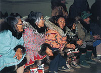 Photograph of an Inuit women watching a drum dance at Coppermine, October 1985.