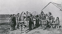 Black and white photograph of a group of Inuvialuit Inuit dancing in traditional attire.