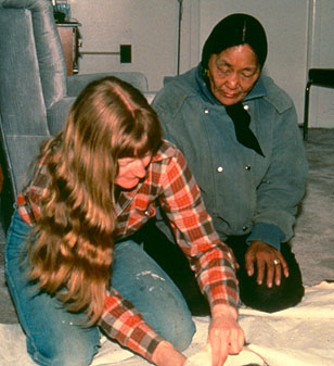 Photograph of Dr. Jill Oakes scraping caribou skin under the instruction of Ulayok Kaviok.