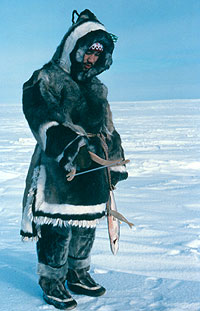 A photograph of an Ungava Inuit man in a traditional seal skin parka and trousers.