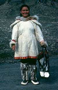 Photograph of Qumanagpik Muckpa wearing caribou skin boots and holding sealskin boots.