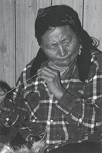 Photograph of an Inuit woman preparing sinew for sewing by moistening it with her lips.