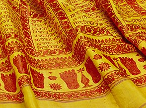 Devotional silk shawl with woven designs of feet and religious text in 	Bengali script. This type of shawl was usually worn by Hindu priests who prayed to Kali, goddess of destruction. The text gives Kali's various names, including Bhuvneshwari, Chandi and Bhadrakali.Varanasi, early 20th centuryP88.45Photo: Peter Paterson