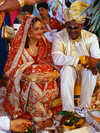 Photograph of a bride and groom at a Hindu wedding in traditional dress.