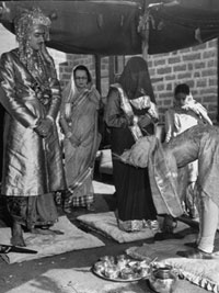 Indian Prince of Mandi of the Rajput caste standing with his veil-covered bride as the groom's younger brother presents her with a pair of shoes, under a canopy during their wedding ceremony in the garden of the bride's home.