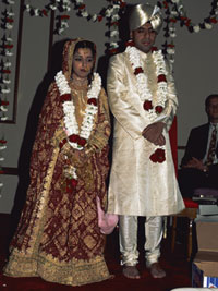 A Hindu bride and groom stand together at their traditional wedding ceremony.
