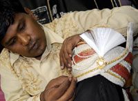 An Indian designer makes a Paghdi, or groom's cap, which is especially made for Hindu and Muslim weddings, at his workshop.