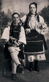 Photography of Macedonian bride (standing) and groom (seated) in traditional wedding costume.