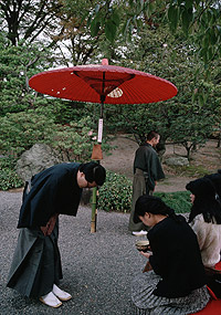 Photograph of a man in kimono and wearing zori bows to a woman, after handing her a bowl at demonstration of a Japanese tea ceremony.