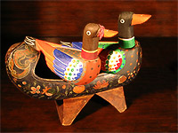 Photograph of a pair of wood-carved, painted ducks.