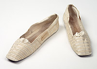 Ivory coloured satin flat shoes with ribbon applique, upper of ecru silk and bands of decorative ribbon applied transversally across front part and longitudinally along quarters.