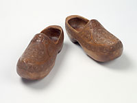 Carved wooden clogs, blunt pointed upturned toe.