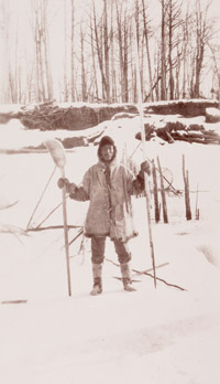 Ingalik man holding an ice chisel in his left hand and an ice scoop in his right, used in winter fishing for cutting hole in the ice and clearing the hole of chipped ice.